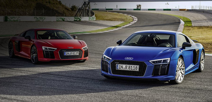 Two 2017 Audi R8s, one blue and one red, sitting on a racetrack.