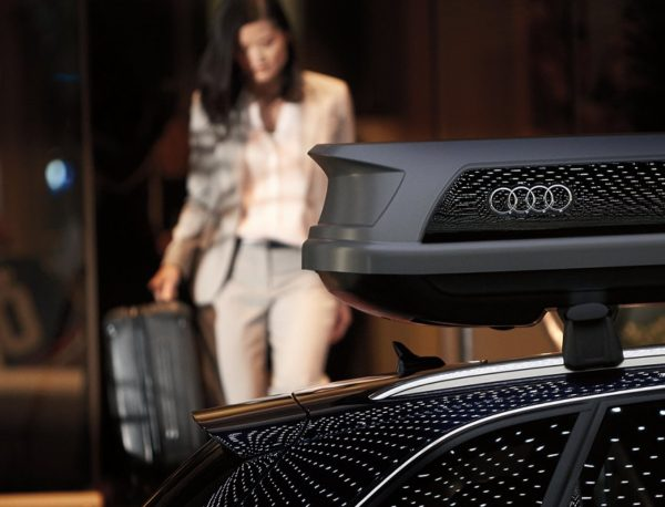 woman walking with suitcase to Audi with Audi roof rack