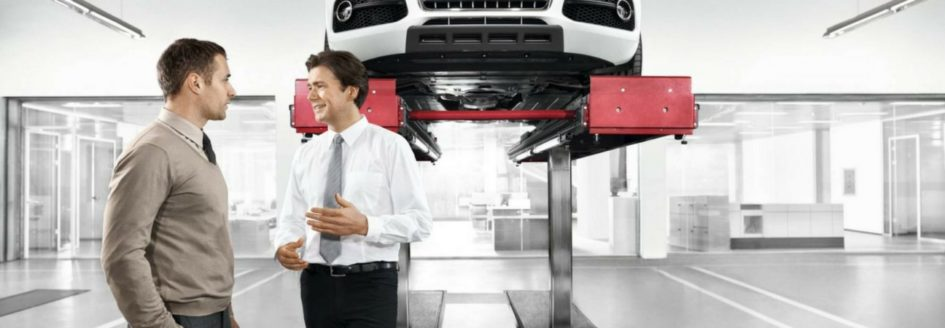 Two men talking under an Audi lifted in a service bay featured in a blog about oil changes