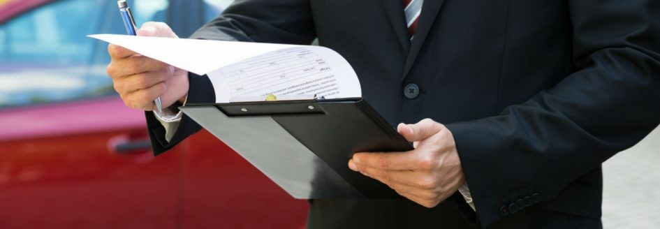 A close-up of a man holding a clipboard featured in a blog post about Audi's certified pre-owned program